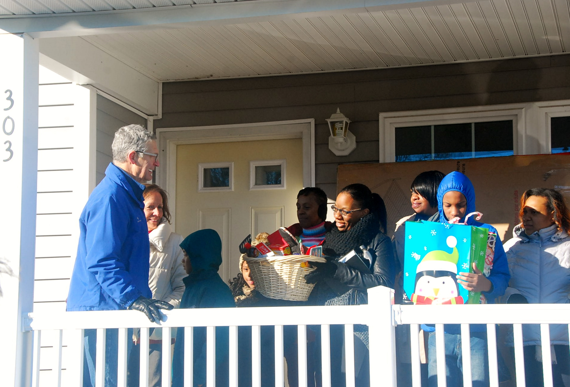 Michael Leader and Becky Bennington from SNC Lavalin present new homeowner, Tasha, with a housewarming basket.