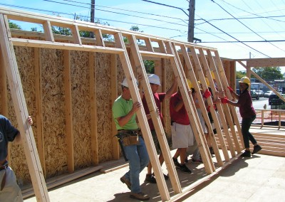 Volunteers and future homeowner, Tasha, framing